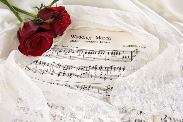 wedding-song-trends - Picture of sheet music with two roses and lace.